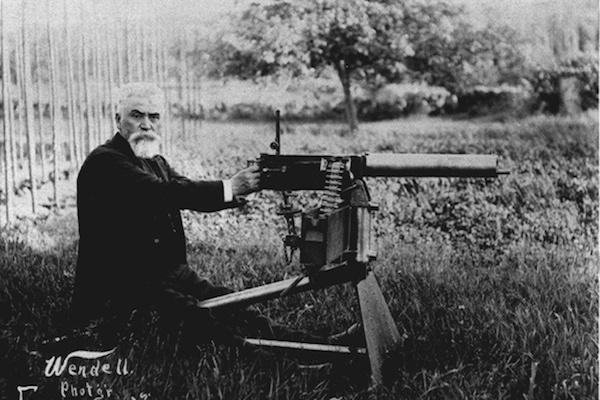 Hiram Maxim with his invention